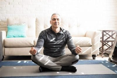 man meditating in living room to reduce stress and prevent stroke
