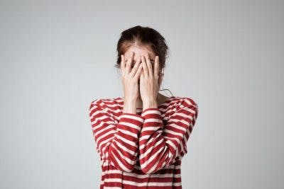 woman covering face because she is embarrassed about her mood swings