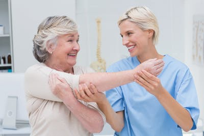 physical therapist with SCI patient practicing stretches to reduce pain