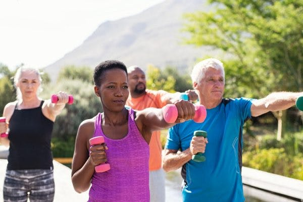 stroke patients exercising in the park using light weight dumbbells