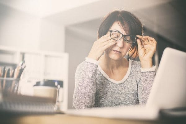 Woman rubbing her eyes at her desk looking tired because she has fatigue after brain injury