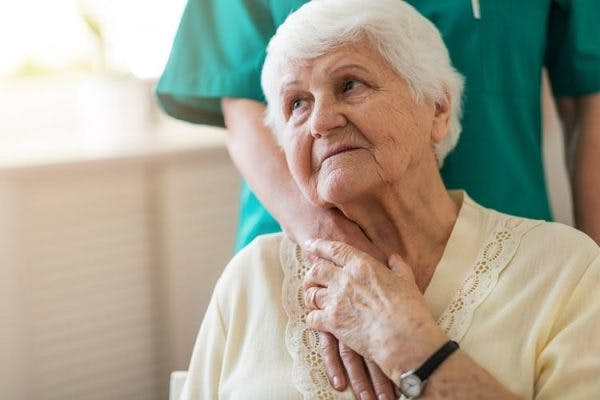 Close-up of elderly post-stroke dementia patient holding her caregiver's hand which is on her shoulder
