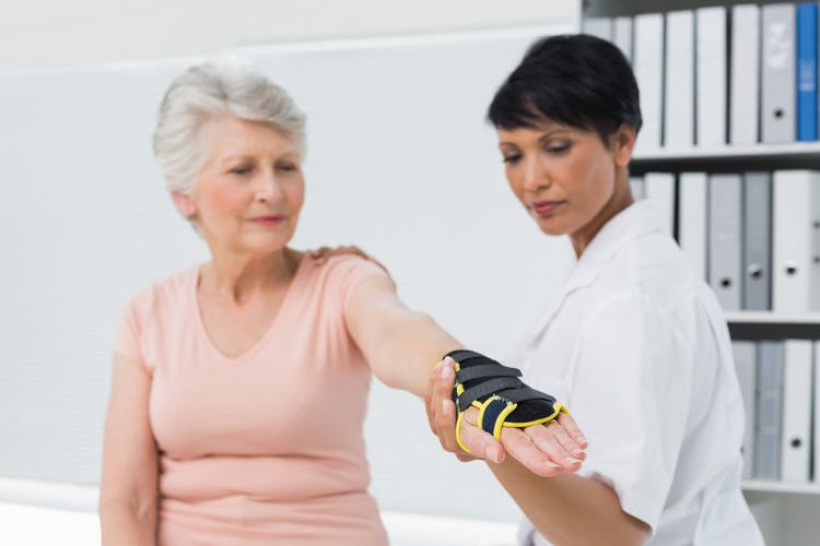 Doctor helping stroke patient try on different types of gloves for stroke patients
