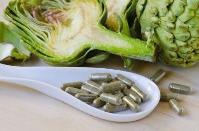 Gericht mit Vitaminkapseln auf Tisch mit Artischocken im Hintergrund