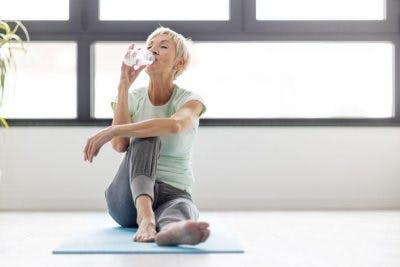 gesunder Schlaganfallpatient nippt an Wasser, während er zu Hause auf Yogamatte entspannt
