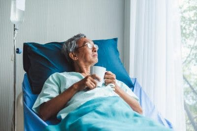 man looking out of hospital room window drinking coffee