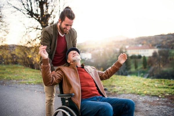 son pushing wheelchair of elderly father who has hemiplegia and hemiparesis through the park