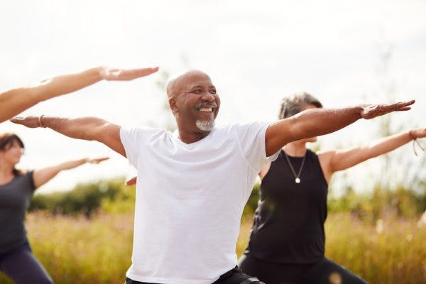 Senior man doing group yoga in park to promote a successful mini-stroke recovery