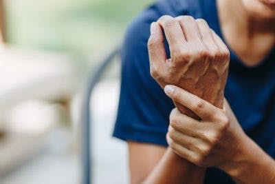Woman rubbing stiff wrist because she has spasticity after TBI