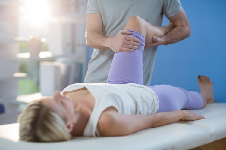 Therapist stretching woman's knee to treat her spasticity after TBI