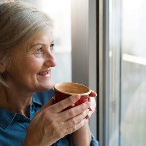 Stroke survivor holding coffee cup and looking out window