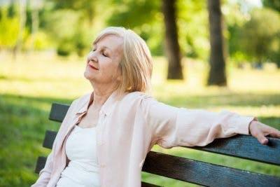 friedlich aussehende Schlaganfallpatientin, die mit geschlossenen Augen auf einer Parkbank sitzt und sich vorstellt, wie sie sich erholt