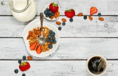 overhead view of bowl of healthy fruit and cup of coffee