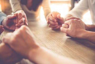 close up of group of people holding hands around table in afternoon light