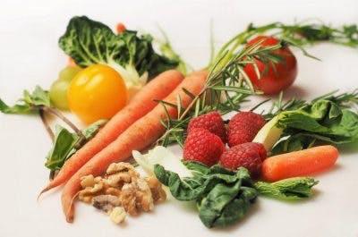 gesunde Karotten, Himbeeren, Walnüsse und Spinat auf weißem Grund