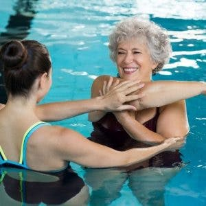 spinal cord injury patient practicing aquatic therapy exercises with PT
