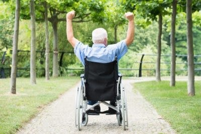 rear view of elderly man in wheelchair lifting arms above his head to celebrate