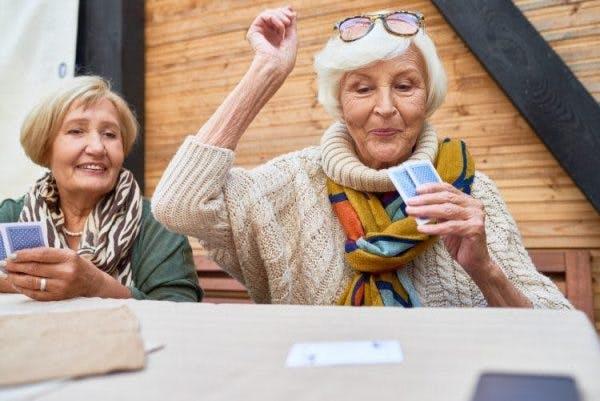 glückliche Frau, die beim Kartenspiel für kognitive Therapie nach Schlaganfall gewinnt