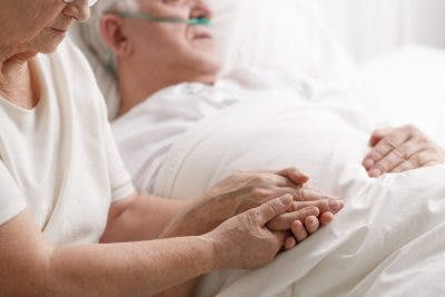 elderly wife holding hand of husband who is in a coma