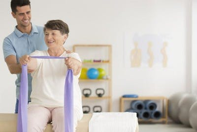 physiotherapist working with stroke patient during rehab exercises