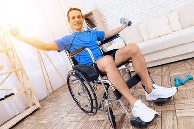 stroke patient in wheelchair holding dumbbells in outstretched arms