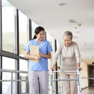 rehabilitation nurse standing next to stroke patient using a walker to recover from paralysis