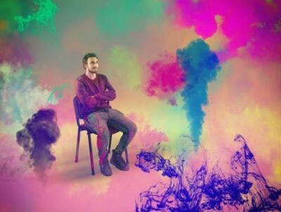 brain injury patient sitting in a chair surrounded by colorful paint to symbolize vivid imagery