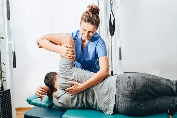 physiotherapist helping tbi patient maximize chances of a full recovery