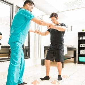 specialist helping patient at physiotherapy for spinal cord injury patients
