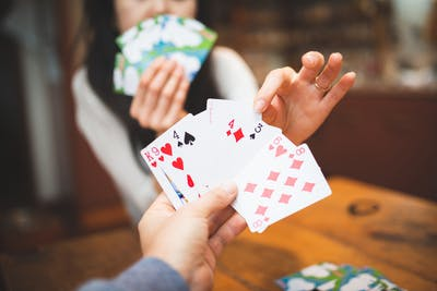 point of view shot of man holding playing cards in his hand while woman  is reaching across table and taking one of his cards