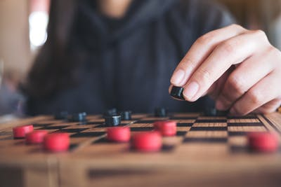 close-up of hand moving checkers piece, one of the best games for stroke patients