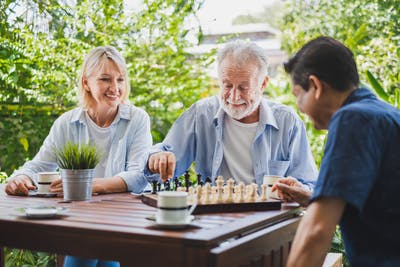 stroke patient playing chess game with his adult son on table outside while adult daughter watches