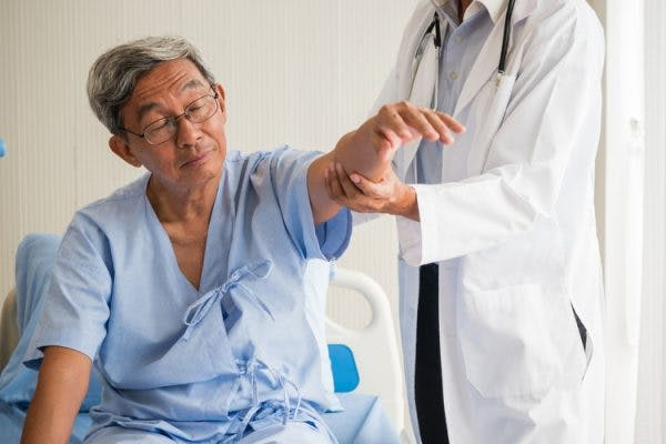 Doctor testing stroke patient's arm for learned nonuse