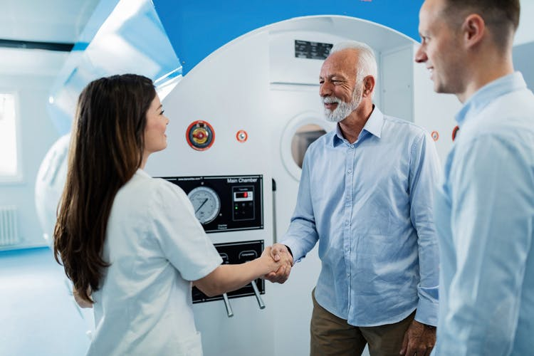 senior man shaking hands with nurse in front of hyperbaric oxygen therapy chamber that he will use to treat his brain injury
