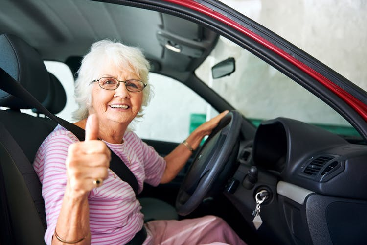 elderly grandma sitting behind the wheel of her car with the passenger door open, smiling at the camera and giving a thumbs up because she can drive again after a stroke