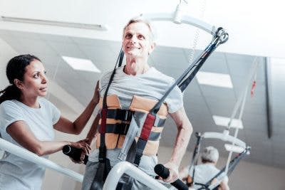 man using walking harness while listening to music as part of his TBI music therapy