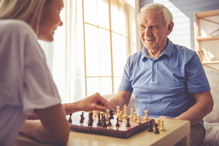 Grandfather and granddaughter playing chess, one of the best games for stroke patients