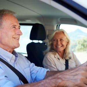 senior man driving for the first time after his stroke, his wife is in the passenger seat smiling at him
