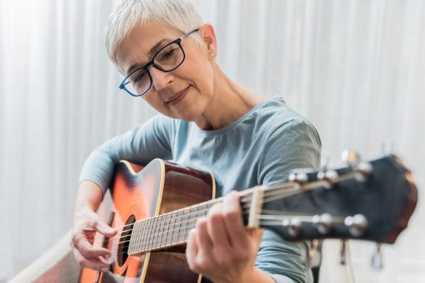 Senior woman playing guitar as part of her TBI music therapy program