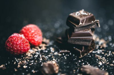 pieces of dark chocolate and raspberries on a black marble counter