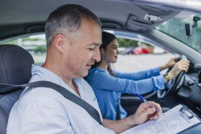 woman taking a driving test while driving instructor writes on his clipboard