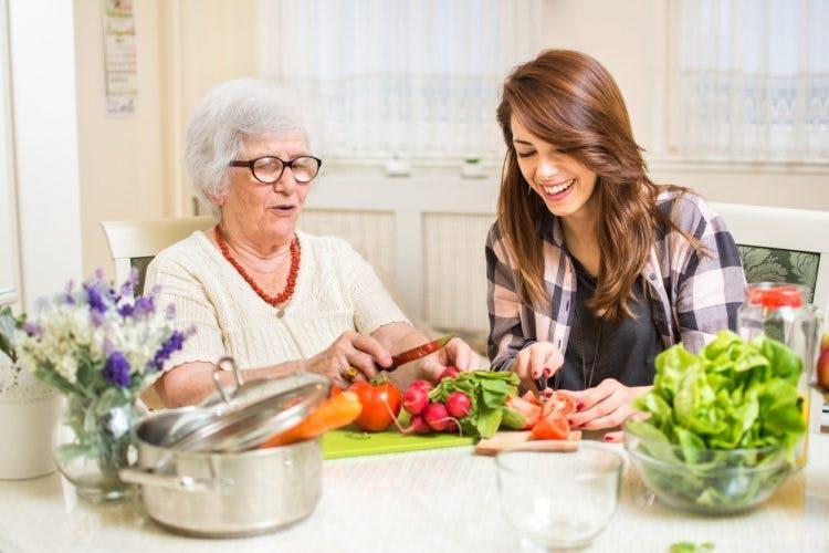 brain injury patient preparing healthy foods in kitchen with caregiver