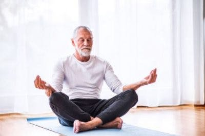 man with spinal cord injury practicing yoga on mat