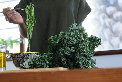 woman eating spinach pasta and kale