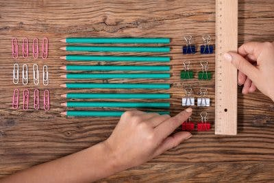 person aligning pencils and paper clips because they suffer from OCD, another mental health disorder that can occur after brain injury
