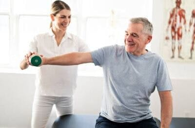 therapist helping stroke patient with arm exercises to prevent learned nonuse