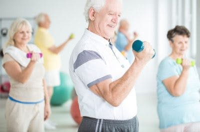 senior man exercising with a dumbbell using massed practice at home