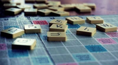 scrabble board with various scrabble tiles scattered on it