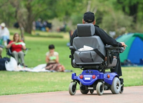 spinal cord injury patient using adaptive equipment like power wheelchairs to improve mobility