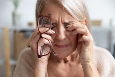 senior woman holding glasses and rubbing her eyes